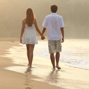 Девушка и парень идут по пляжу